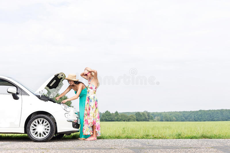 Female friends examining broken down car on country road against clear sky stock photo