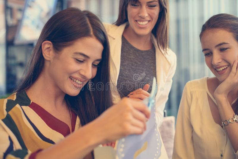 Female friends giving birthday gift. Girl opens her present. Lifestyle royalty free stock photography