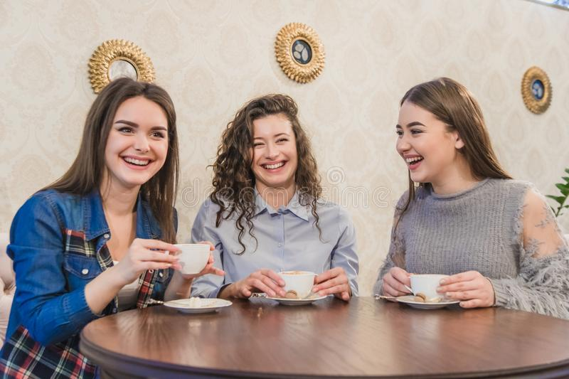 Female friends having a coffee together. Three women at cafe drinking, talking, laughing and enjoying their time royalty free stock photo