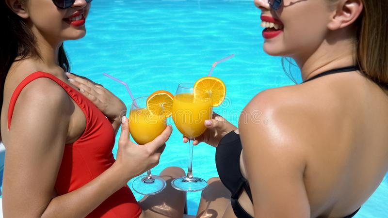 Female friends having fun at poolside and drinking cocktails, summer pool party royalty free stock photo