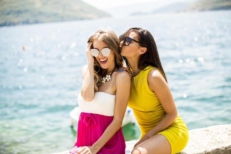Female friends having fun on the sea shore on sunny day royalty free stock photography