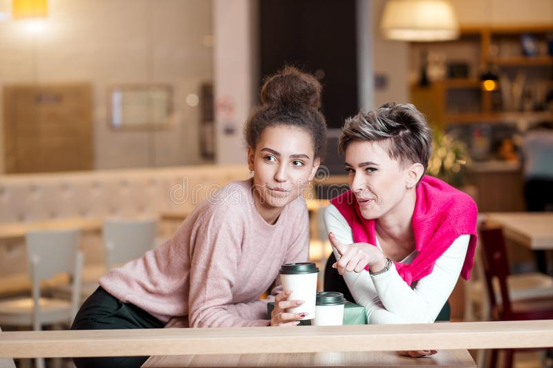 Female friends having lunch at mall cafe laughing and smiling after shopping stock photos
