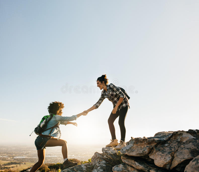 Helping Each Other: Female Friends Hiking Help Each Other In Mountains Stock