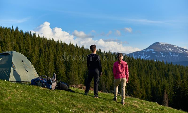 Female friends hiking together in the mountains. Rearview shot of women tourists enjoying on top of a hill after hiking taking in the view camping site people royalty free stock image