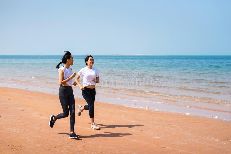 Female friends running on the beach. On a sunny day women sea seaside asian workout jogging sportswear jogger sand track runner training athletic two girls royalty free stock photography