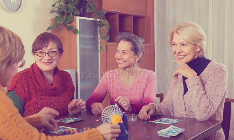 Female friends on summer terrace. Portrait of smiling mature female friends on summer terrace. Focus on brunette female stock photos