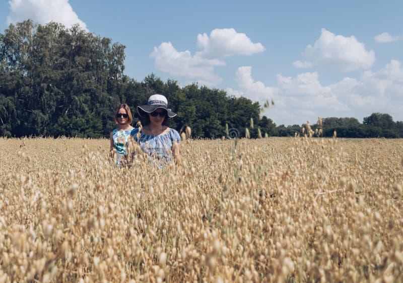 Female friends in sunglasses walking through oat field stock images