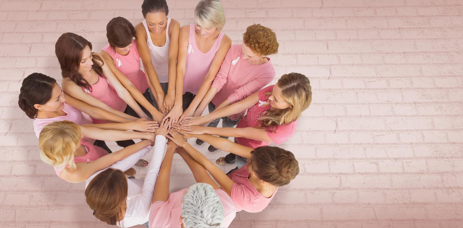 Composite image of female friends supporting breast cancer. Female friends supporting breast cancer against white wall royalty free stock photos