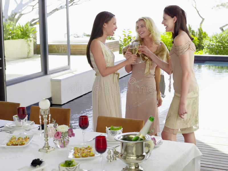 Female Friends Toasting Champagne Flutes At Dinner Party royalty free stock images