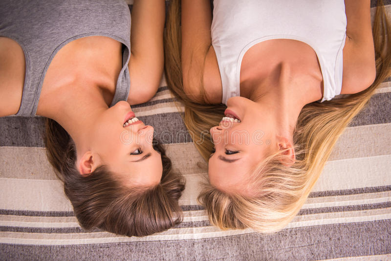 Female friends. Top view of two female friends are lying on bed and laughing royalty free stock photography