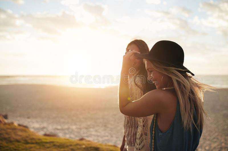Female friends walking on the sea shore stock photos