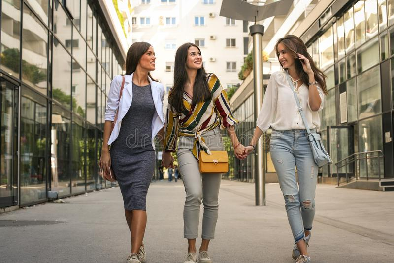 Female friends walking street, holding hands. stock images