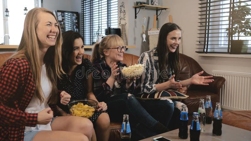 Female friends watch comedy film at home on TV. Happy girls laugh watching funny action movie together 4K slow motion. Beautiful ladies share togetherness stock photos