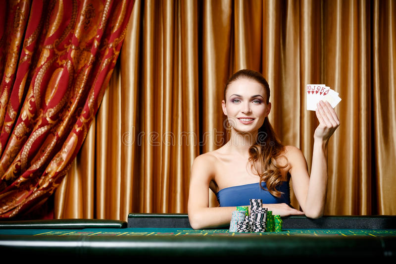 Female gambler at the poker table. Portrait of the female gambler at the poker table handing cards stock image