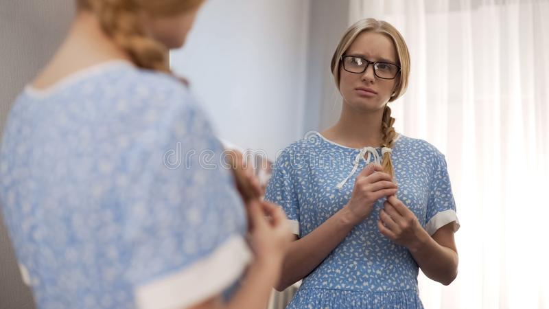 Female geek in glasses looking in the mirror, feeling bad of poor appearance stock images