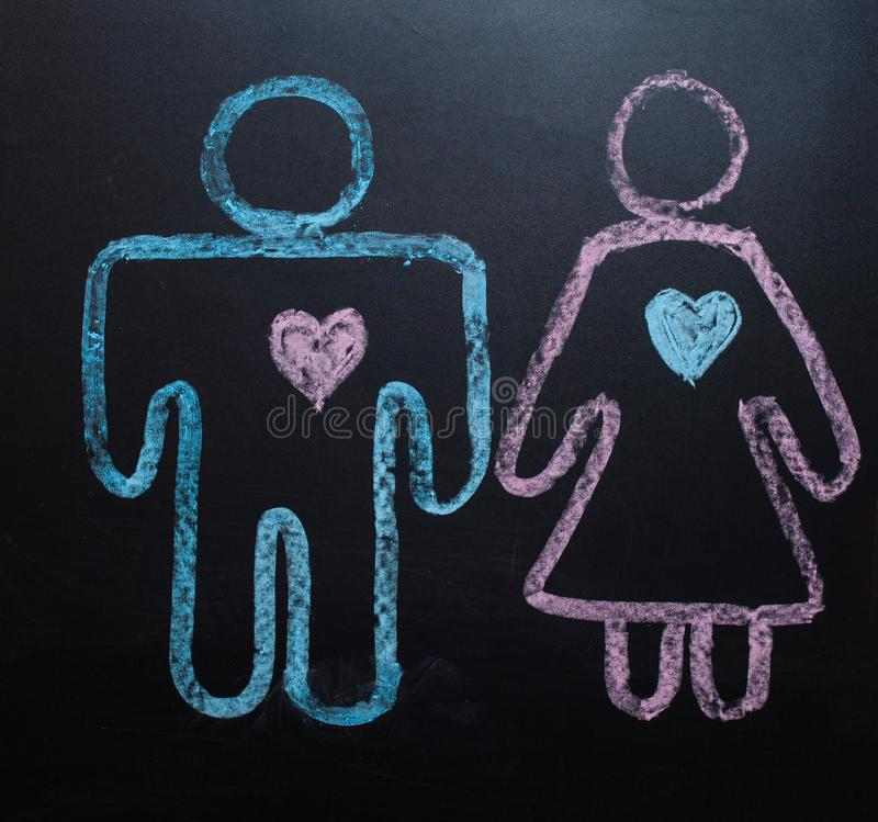 The female gender symbol is equal to the male concept of gender equality. Drawing with chalk on the chalk Board. The female gender symbol is equal to the male stock image