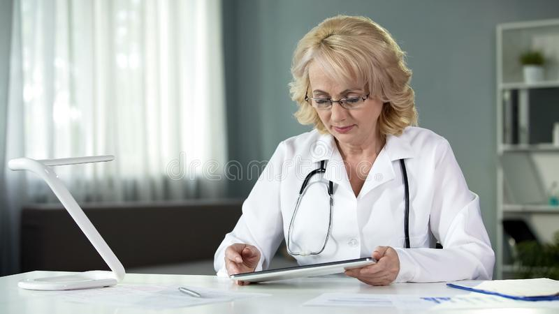Female general practitioner reading patient's online medical records on tablet. Stock photo stock photos