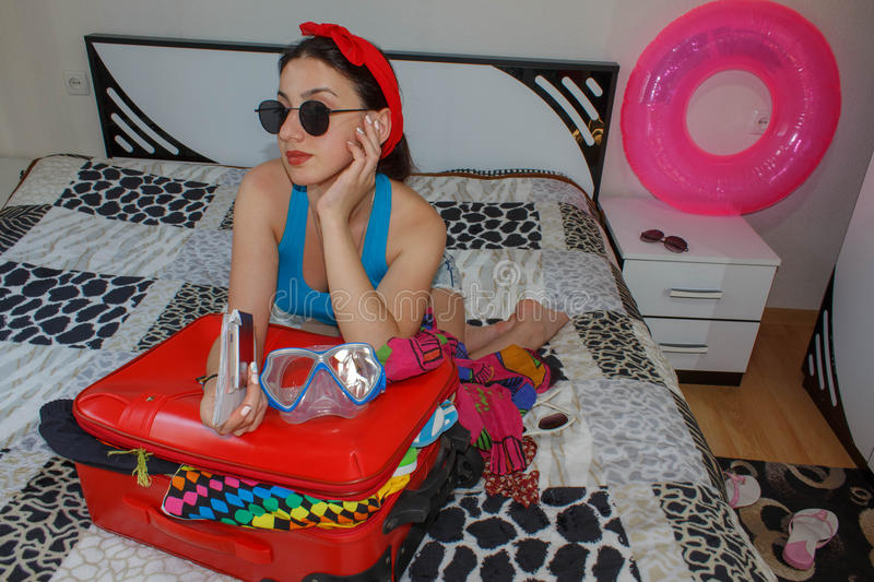 Female Getting Ready For Traveling. young beautiful woman, red suitcase, sitting, waiting, summer vacation, colorful, traveling ar royalty free stock photos