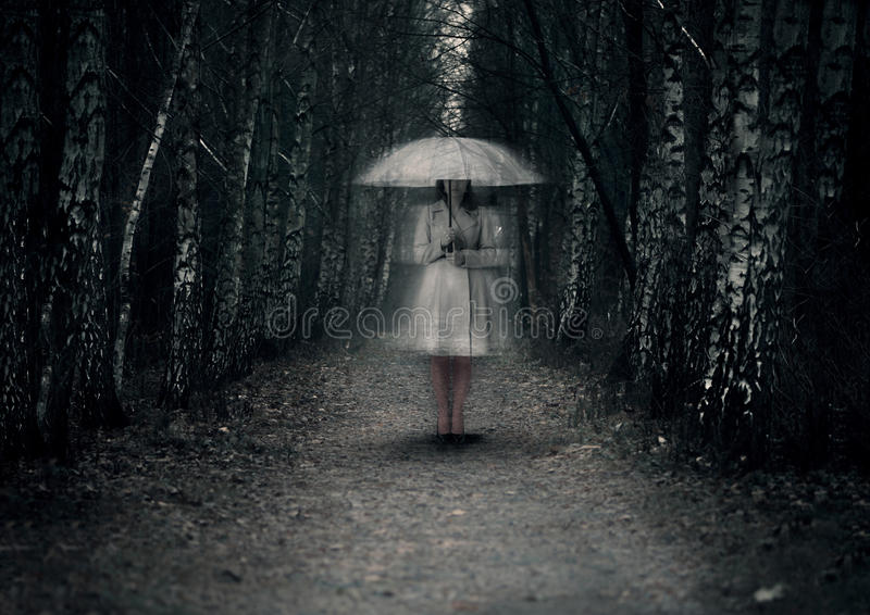 Female ghost stands on a dark path. Ghost woman stands on a dark path in the forest stock images