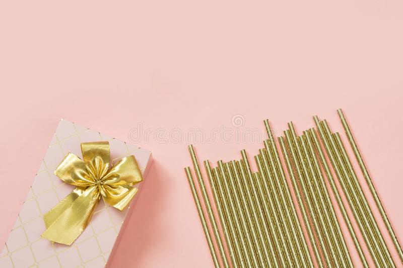 Female gift box with golden ribbon and cocktail accessories on punchy pastel pink. Copy space. stock image