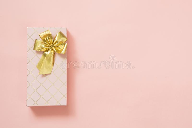 Female gift box with golden ribbon on punchy pastel pink. Birthday. Copy space. stock images
