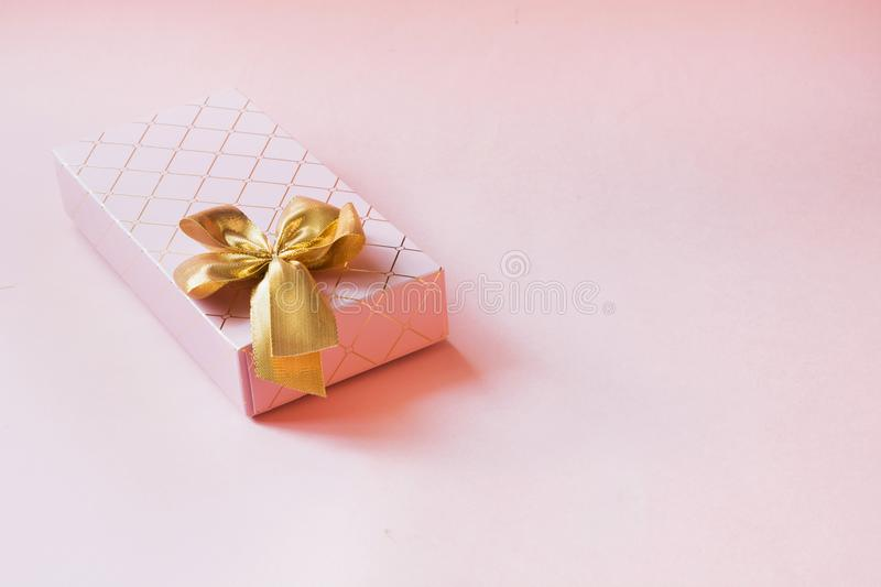 Female gift box with golden ribbon on punchy pastel pink. Birthday. Copy space. royalty free stock image