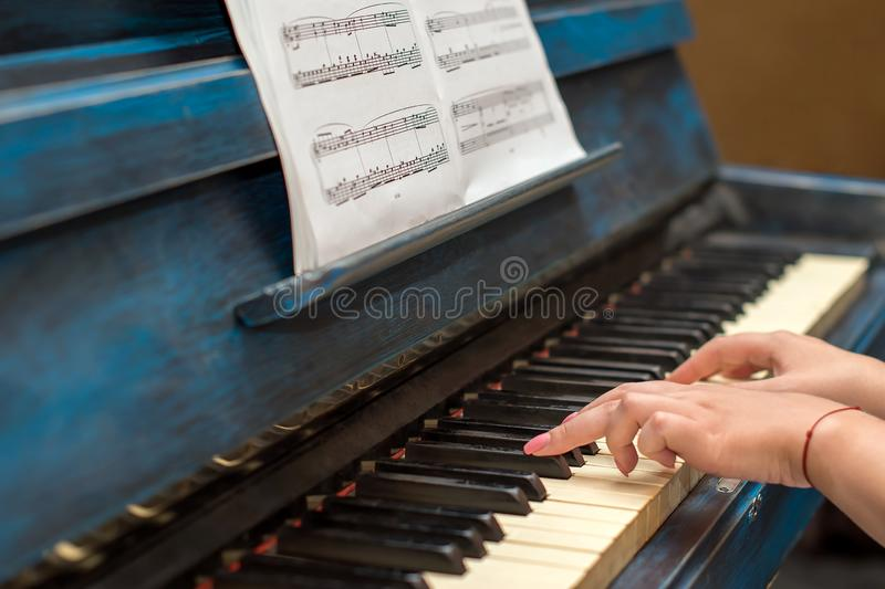 Black and white keys of piano musical instrument. Female girl hands with graceful manicure play old piano keyboard on stock photos