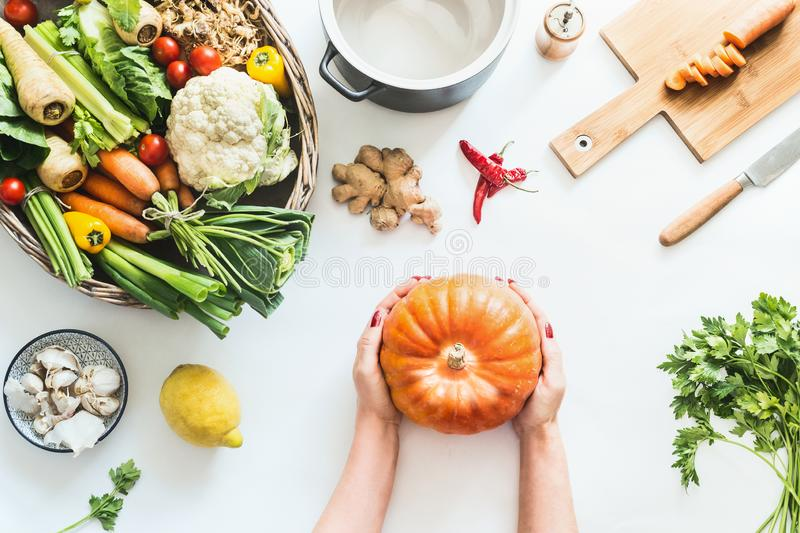 Female girls hands holding pumpkin on white table background with various organic farm vegetables und pot, top view. Seasonal stock photography