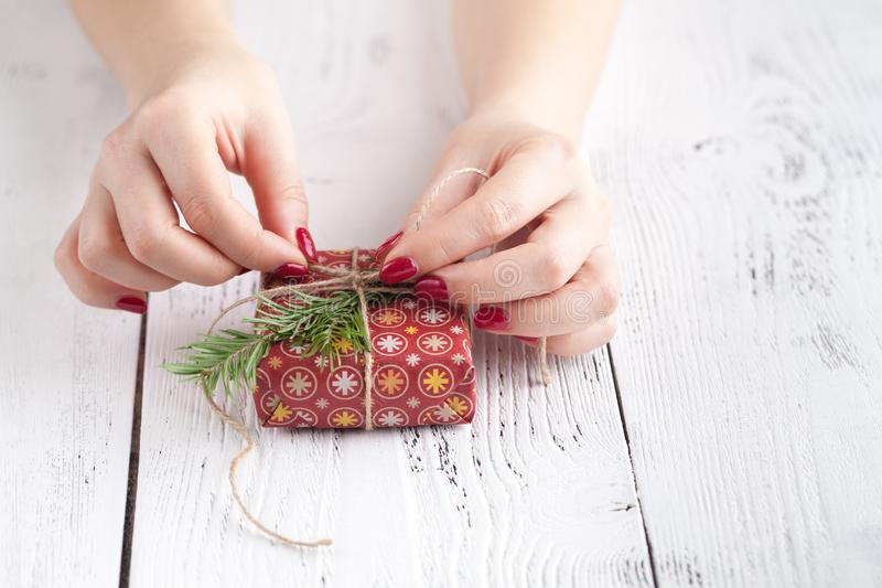 Female give present wrapped craft paper on aged wooden table, holiday gift box. Copyspace from corner royalty free stock photography
