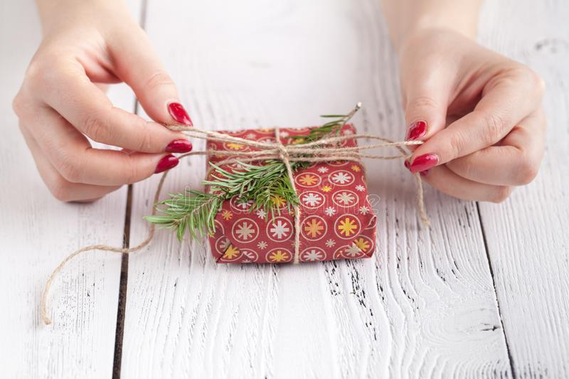 Female give present wrapped craft paper on aged wooden table, holiday gift box. Copyspace from corner stock photos