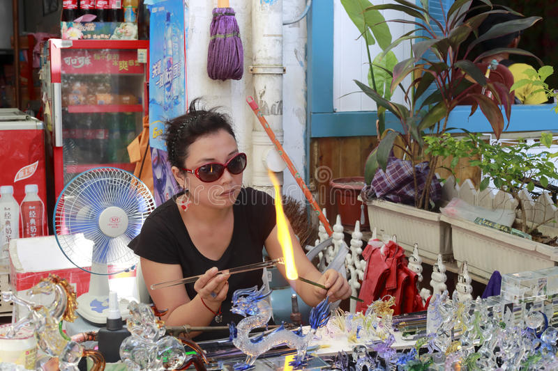 Female glass artist demonstration of making a bottle from a molten glass. Female glazier by the road in gulangyu island,amoy city,china royalty free stock photography