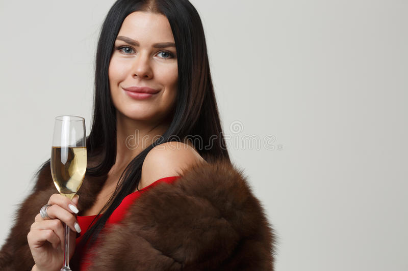 Female with glass of champagne. Beautiful female with glass of champagne in mink coat on blank gray background stock images