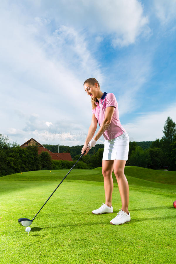 Female golf player on course doing golf swing