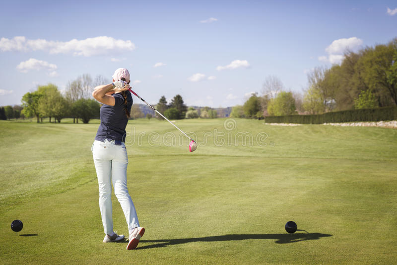 Female golf player swinging club. stock image