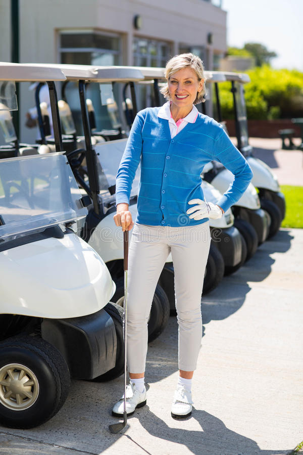 Female golfer beside golf buggy. At the golf course parking stock photo