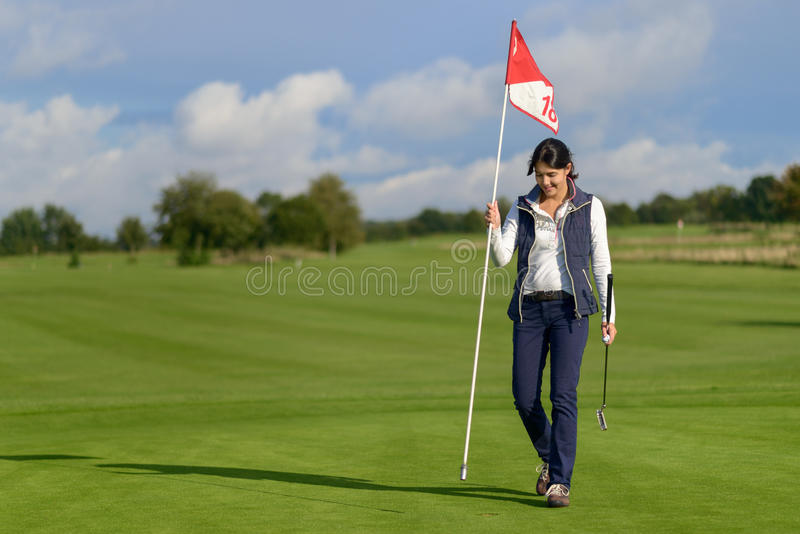 Female golfer holding the flag from the hole royalty free stock photography