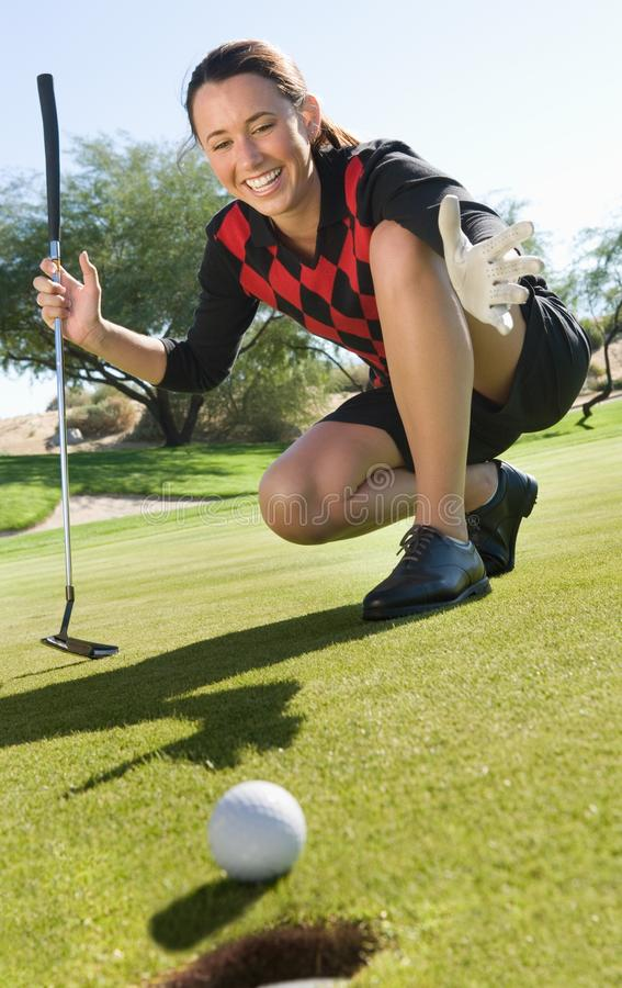 Female golfer looking at ball rolling royalty free stock photos