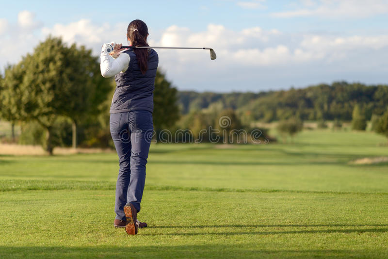 Female golfer striking the golf ball stock photography