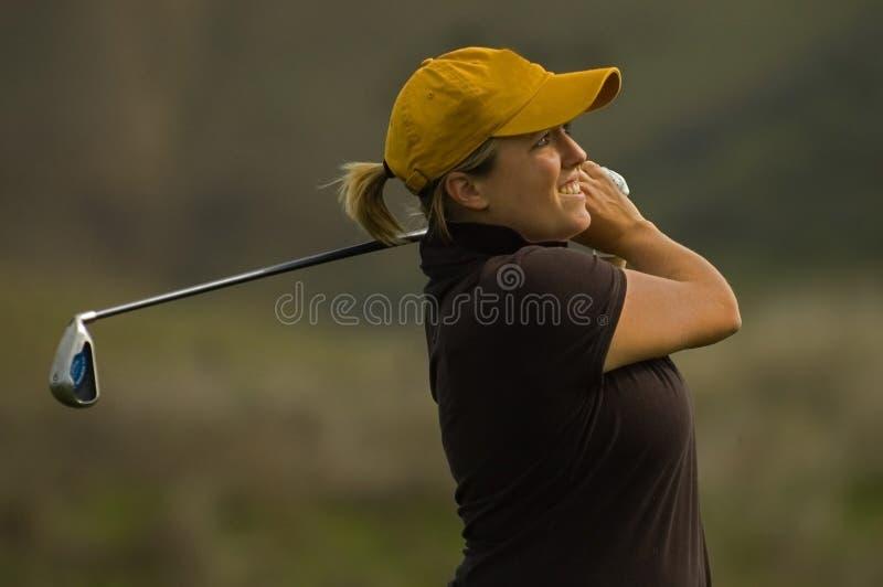 Female golfer swinging iron club royalty free stock image