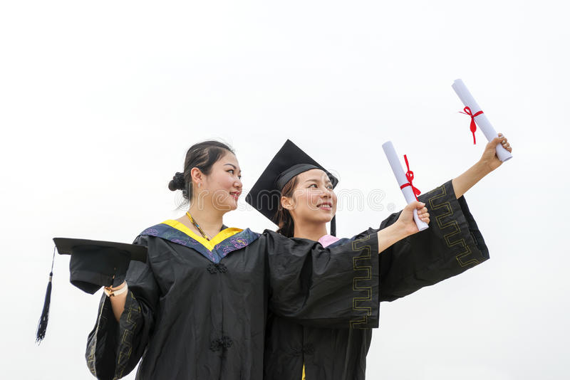 Female graduate wearing graduation gown stock images
