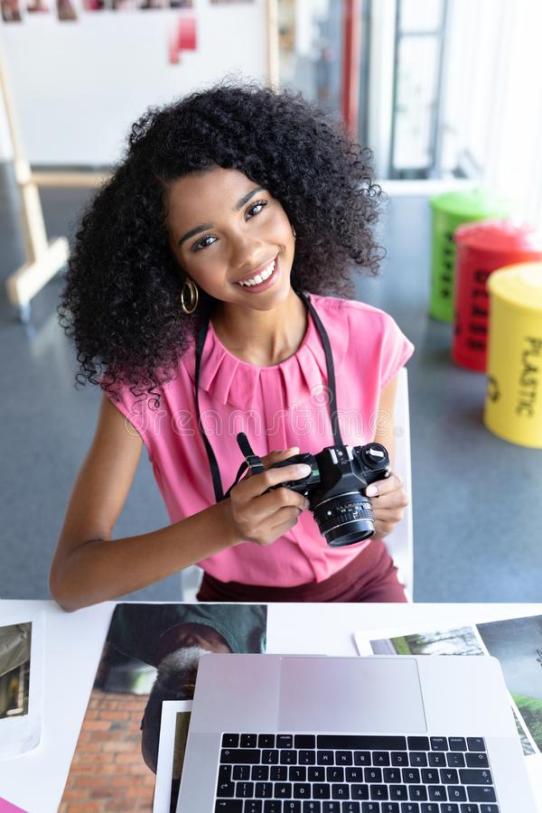Female graphic designer reviewing photos on digital camera at desk in office stock photo