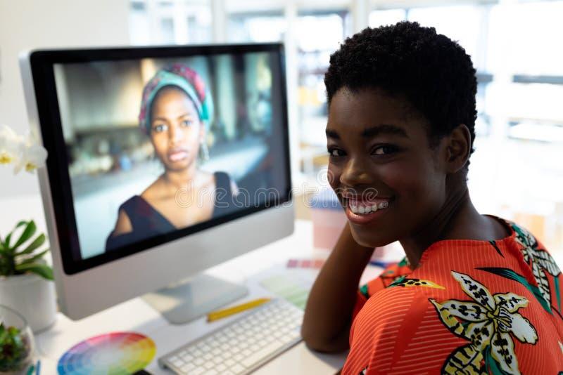 Female graphic designer smiling at desk in office stock images