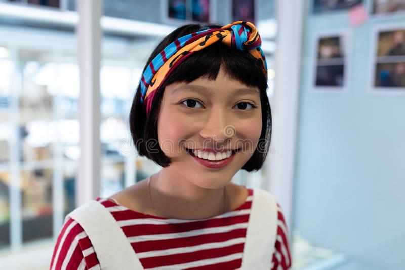 Female graphic designer smiling. Portrait of pretty young Asian female graphic designer smiling in office. This is a casual creative start-up business office for royalty free stock images