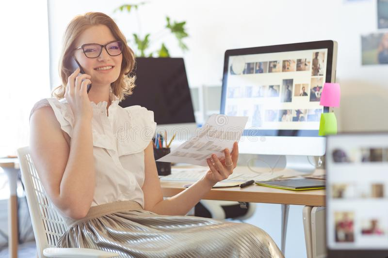 Female graphic designer talking on mobile phone in office royalty free stock photography