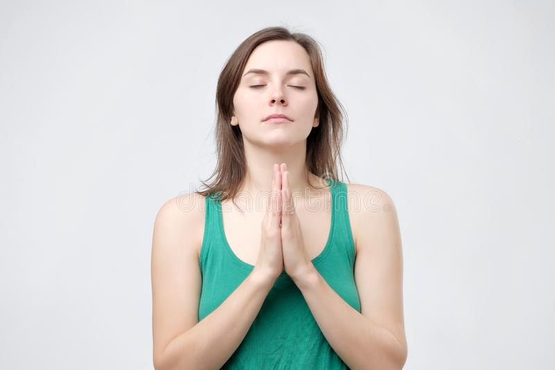Girl prays for wellness of family, keeps palms pressed together in praying gesture. Female in green t-shirt prays for wellness of her family, keeps palms pressed royalty free stock image
