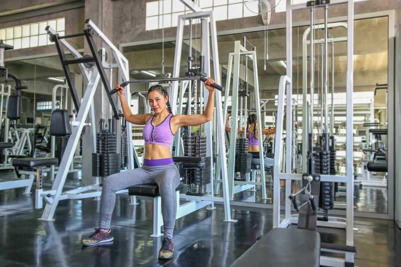 Female in gym. sport, fitness, bodybuilding, woman exercising and flexing muscles on machine in gym. asian girl. Asian girl royalty free stock images