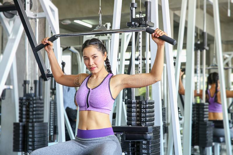 Female in gym. sport, fitness, bodybuilding, woman exercising and flexing muscles on machine in gym. asian girl. Asian girl royalty free stock image