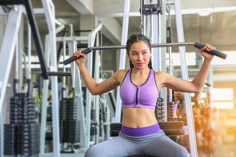 Female in gym. sport, fitness, bodybuilding, woman exercising and flexing muscles on machine in gym. asian girl. Asian girl royalty free stock photography