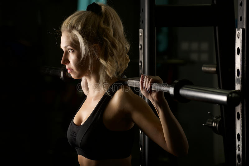Female in the gym. Young beautiful woman works out in the gym stock photos