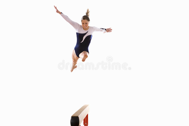 Female gymnast performing jump on balance beam, low angle view royalty free stock image